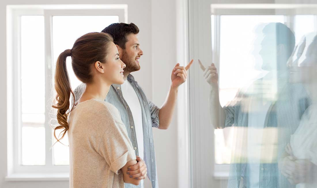 Man and woman couple standing In front of a window smiling after receiving a thorough home inspection