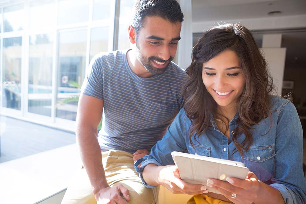 Smiling couple using a tablet to check their online home inspection report