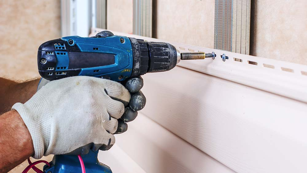 Person using a drill to do maintenance on a house after an issue was discovered while preforming home inspection services